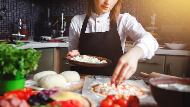 Молодая девушка готовит пиццу
