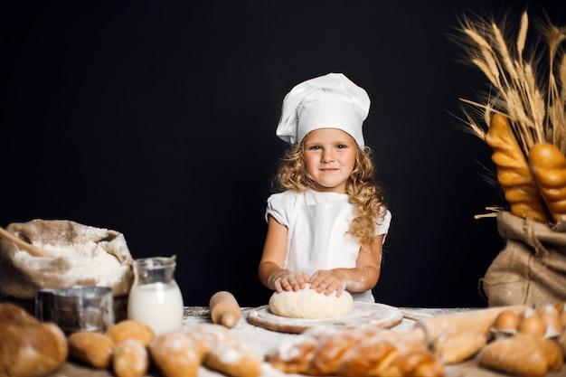 小さな女の子がテーブルで生地を混練