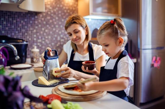 小さな女の子と料理の女性