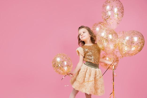 風船の束を持って幸せな若い女の子