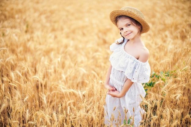 秋の麦畑で幸せな子。白いドレスと麦わら帽子で美しい少女は、遊んで、収穫を楽しんでいます