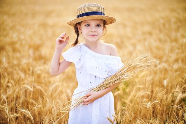 Счастливый ребенок в осенней пшеничном поле. красивая девушка в белом платье и соломенной шляпе развлекается, играя, собирая урожай