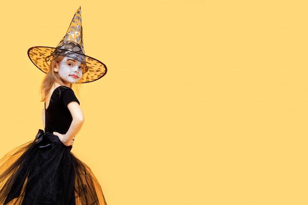 魔女の衣装で自慢している小さな女の子