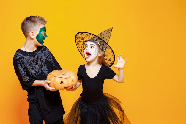 パンプキンと遊ぶハロウィーンの衣装の子供たち