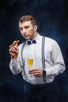シャンパンと葉巻のグラスを持つエレガントな男