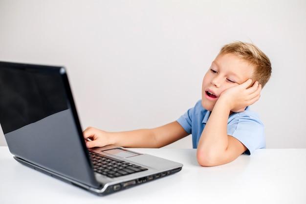 テーブルでラップトップを使用して退屈した子供