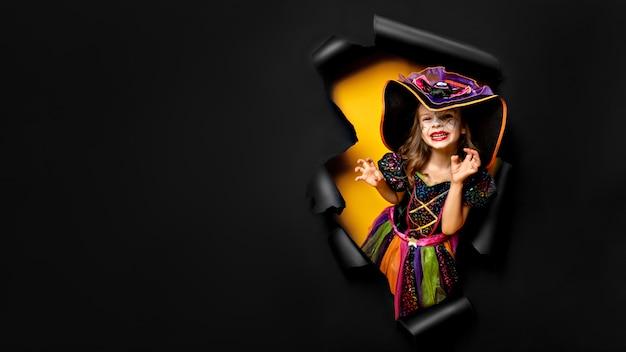 Смеется смешная детская девочка в костюме ведьмы в хэллоуин