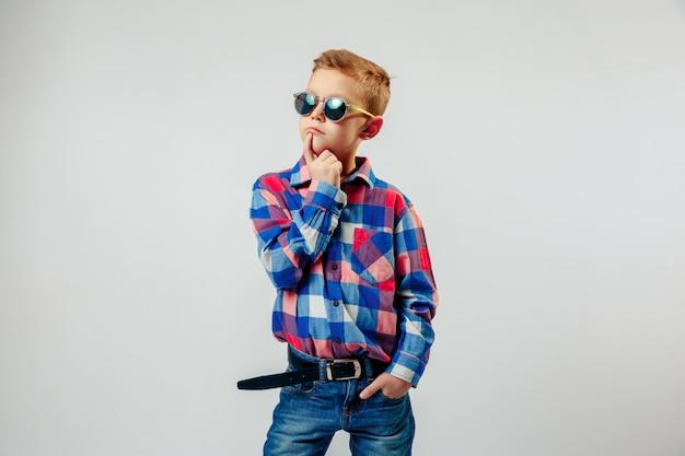 Мальчик одет в красочную клетчатую рубашку, синие джинсы, кеды, солнцезащитные очки, позирует и развлекается
