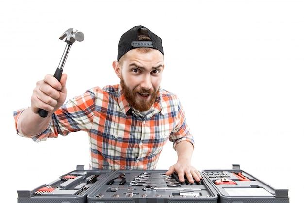 若いひげを生やした男は、修復ツールを保持します