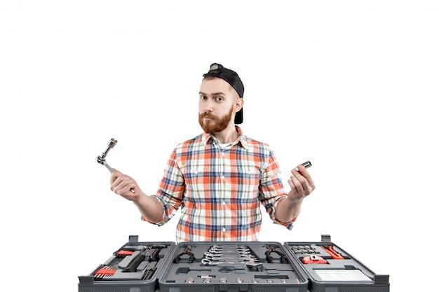 Молодой бородатый мужчина проводит ремонт инструментов