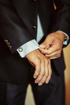 Мужчина пристегивает манжеты своей рубашки.