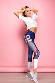 ジムトレーニングのスポーツ服を着て形で完璧なボディを持つ美しいフィットネスセクシーな女性。