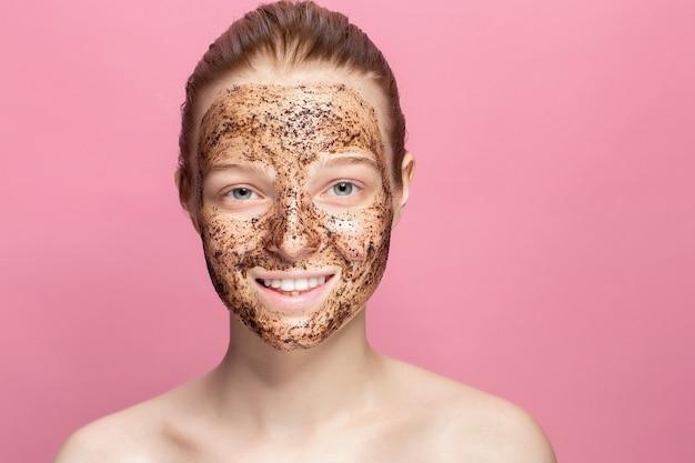 フェイススキンスクラブ。自然なコーヒーマスク、顔の肌の顔のスクラブを適用するセクシーな笑顔の女性モデルの肖像画。美容製品で覆われた顔を持つ美しい幸せな女性のクローズアップ。