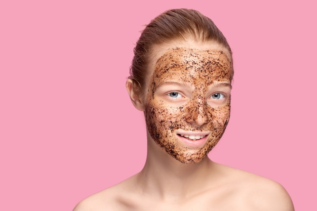 Скраб для лица. портрет сексуальные улыбающиеся девушки модели, применяя натуральный кофе маски, скраб для лица на коже лица. макрофотография красивая счастливая женщина с лицом, покрытым продуктом красоты.