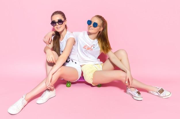 Молодые подростки сидят на скейтборде