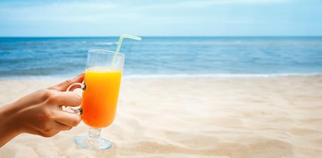ぼやけた海のガラスにジュースを持っている手
