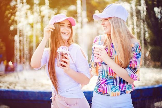 Веселые женщины с напитками возле фонтана