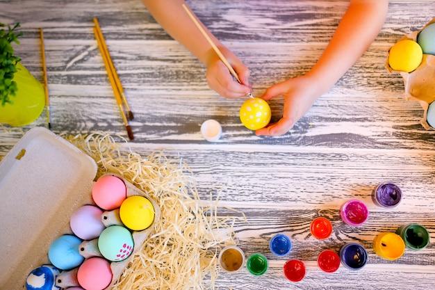 子供の手は白と黄色の色のイースターエッグでペイントします。家族のイースターの準備。イースターエッグを持つ少女の手。閉じる