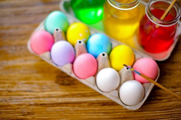 バスケットでカラフルな卵とハッピーイースター。休日の装飾テーブル。上面図。