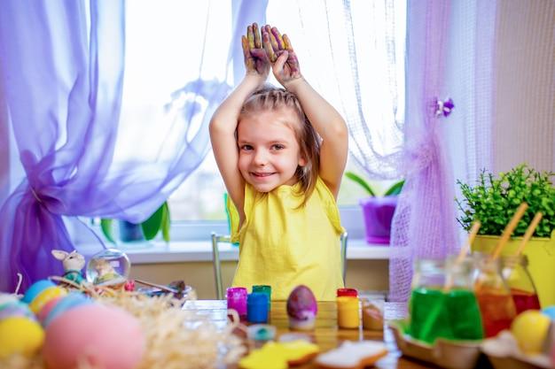 卵を塗るバニーの耳、自宅で小さな子供に幸せなイースターの女の子。春休み