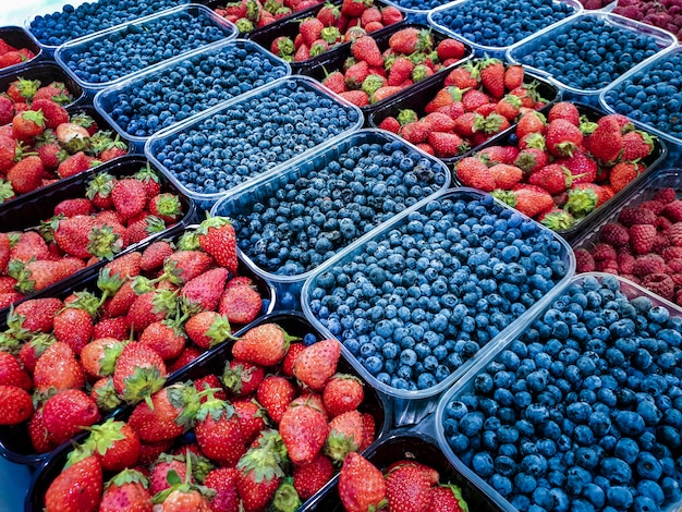 Различные свежие ягоды фрукты в пластиковых лотках на прилавке продовольственного рынка