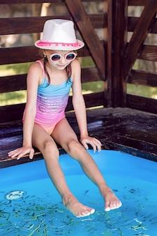 Молодая девушка получает массаж с рыбками. пилинг с рыбой. девушка наслаждается лечебной процедурой. массаж ног с рыбами в аквариуме крупным планом. рыбная спа-процедура.