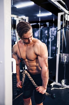 上腕三頭筋の重量運動をしているハンサムな筋肉フィットネスボディービルダー