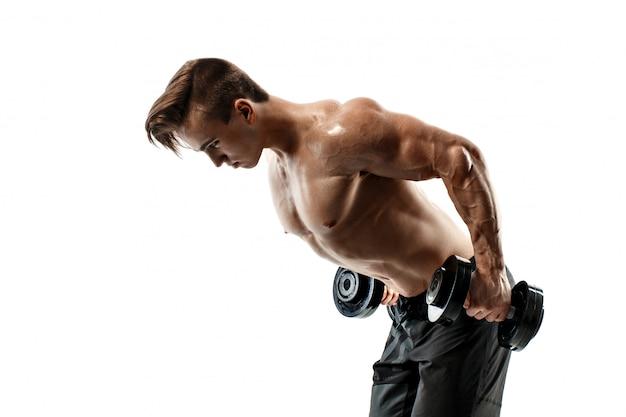 白い背景の上にダンベルでのエクササイズを行う筋肉ボディービルダー男