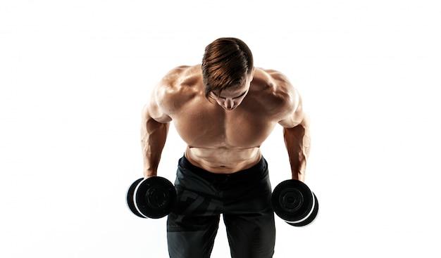 Мускулистый парень культурист делает упражнения с гантелями на белом фоне