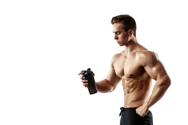白い背景の上のシェーカーでタンパク質ドリンクを飲みながら筋肉男