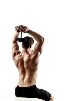 背中の筋肉とダンベルで手をポンピングトレーニングでスポーティな男。