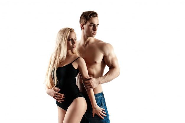 セクシーなカップルは、白い背景で隔離された美しい女性を保持している筋肉の男