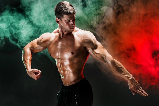 上半身裸のボディービルダーの肖像画。スタジオでポーズをとって筋肉の男。