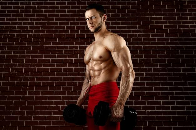 Сильный злой мускулистый парень позирует с гантелями