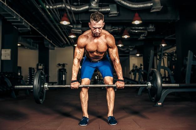 ジムでデッドリフト運動を行う若い上半身裸の男。
