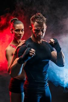 Сильный боксер в стойке с повязками на кулаках с девушкой, стоящей за ним.