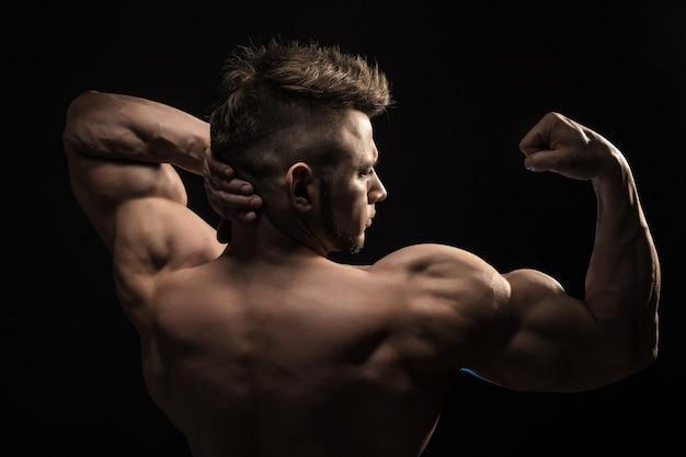 背中の筋肉をポーズ強い運動男性フィットネスモデル。