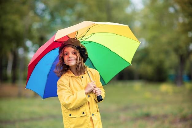 Счастливая смешная детская девочка с многоцветным зонтиком в резиновых сапогах в осеннем парке