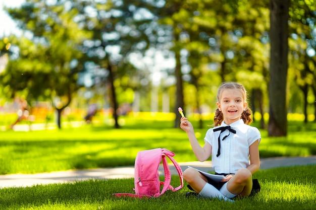 ビンゴ。レッスンと思考のアイデアの後草の上に座っているピンクのバックパックと小さな学校の女の子、本を読んでレッスンを勉強、メモ、教育、学習の概念を書く