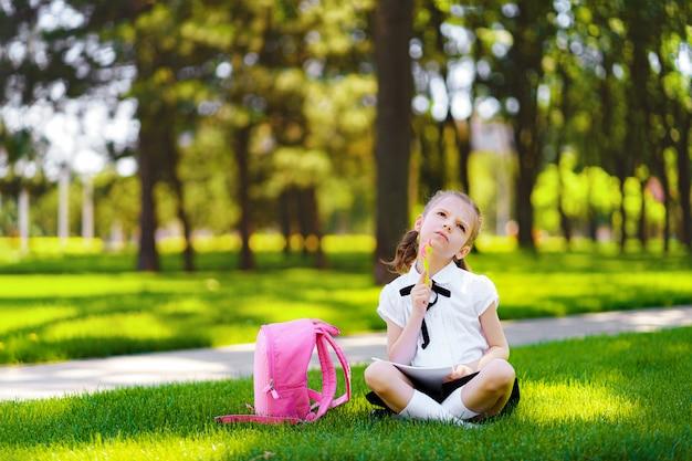 Маленькая школьница с розовым рюкзаком, сидя на траве после уроков и идей мышления, читать книги и изучать уроки, писать заметки, концепция образования и обучения