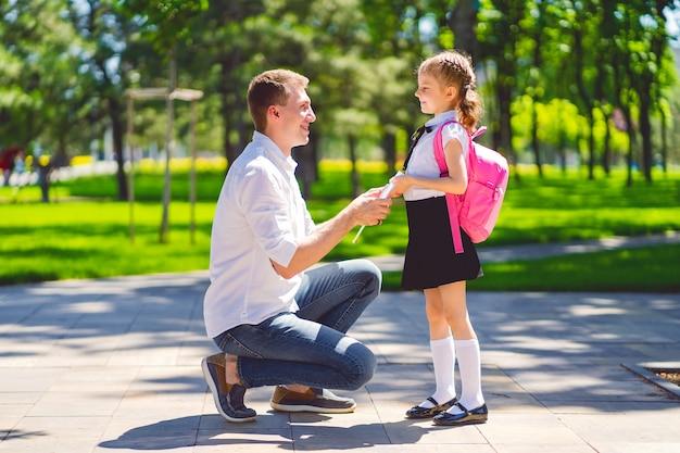 Отец ведет дочь в школу в первом классе. первый день в школе. обратно в школу.