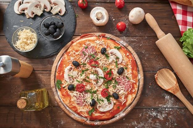 木の板に自家製ピザ、トマトとサラミ、マッシュルーム、古い木製のテーブル、トップビューでイタリアンスタイル