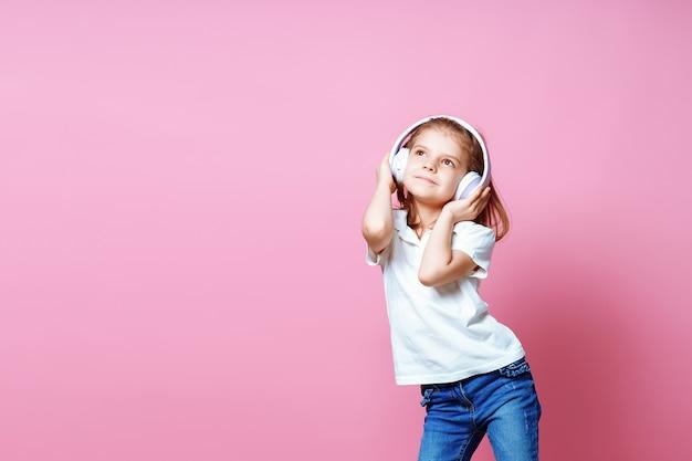 ピンクのヘッドフォンで音楽を聴いている女の子。幸せなダンス音楽、目を閉じて、笑顔のポーズを楽しんでいるかわいい子