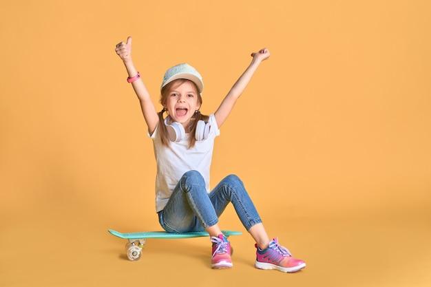 黄色の上のスケートボードとカジュアルでスタイリッシュな小さな女の子子供女の子。