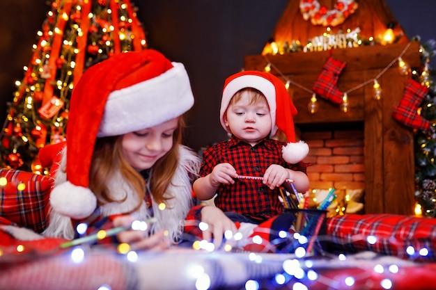 サンタの帽子で面白い女の子がサンタと彼女の兄弟に手紙を書く