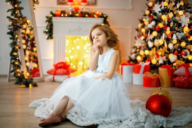 クリスマスに座っている思いやりのある女の子装飾部屋