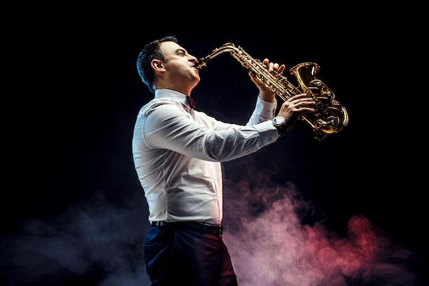 Красивый взрослый мужчина играет на саксофоне