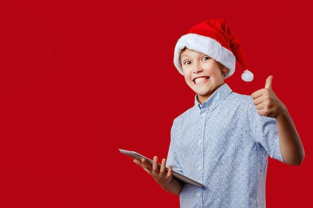 Молодой мальчик санты делая одобренные большие пальцы руки вверх пока держащ таблетку