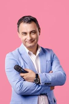 Портрет среднего возраста человека с микрофоном в руке, носить синий пиджак. улыбаясь. изолированный розовый