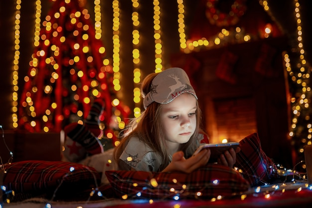 タブレットを使用して周りのプレゼントでカーペットに横たわっている少女